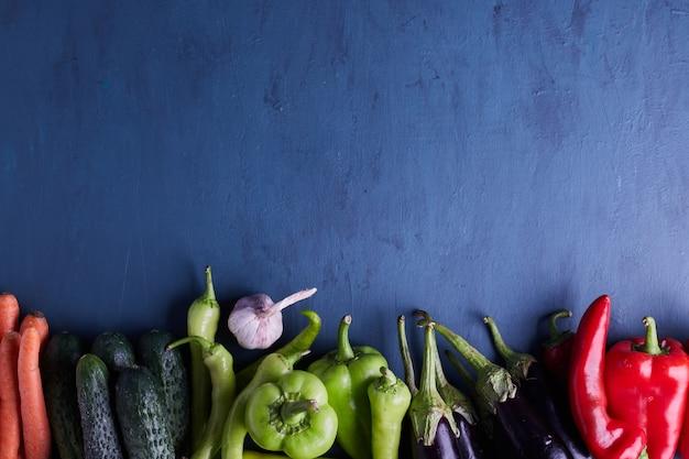 파란색 테이블 하단에 다양한 야채. 무료 사진