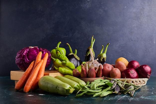青いテーブルに分離されたさまざまな野菜。 無料写真