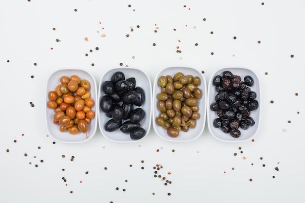 Varietà di olive con le spezie in piatti bianchi sulla vista bianca e superiore. Foto Gratuite