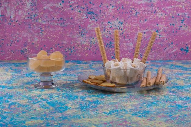 Varietà di pasticcini in tazza di vetro e piatto su sfondo rosa Foto Gratuite