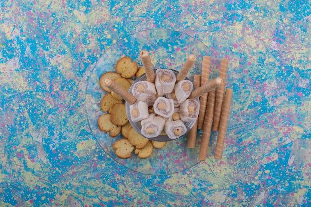 Varietà di pasticcini in tazza di vetro e piatto, vista dall'alto Foto Gratuite