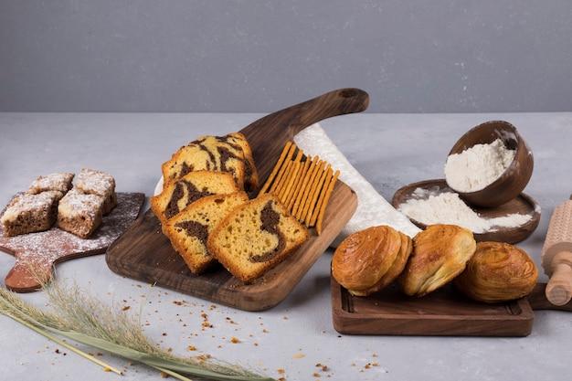 Varietà di pasticcini e cracker su una tavola di legno Foto Gratuite