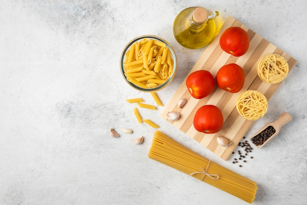 Varietà di pasta cruda, bottiglia di olio d'oliva, grani di pepe e pomodori su sfondo bianco. Foto Gratuite