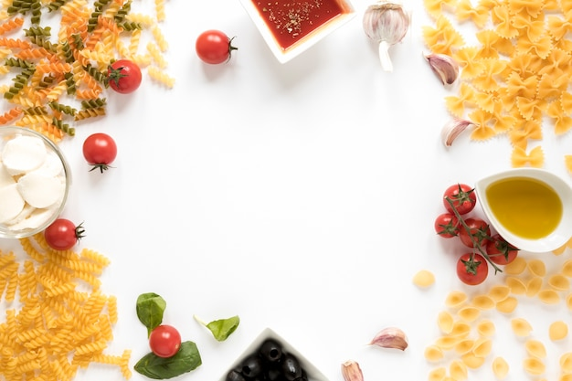 Variety of raw pasta with ingredient on white surface Free Photo