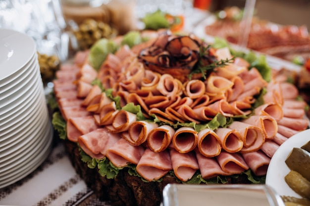 Variety of sliced ham and decorated with salad Free Photo
