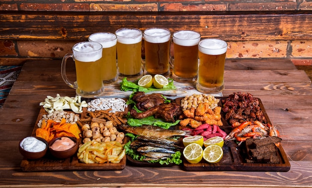 Variety of snacks and nuts with beer cups Free Photo