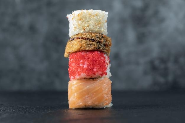 Varietà di rotoli di sushi isolati sulla tabella grigia. Foto Gratuite