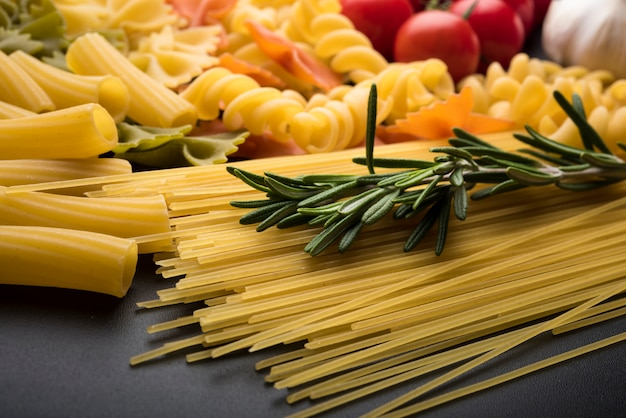 Variety of uncooked pasta on black background Free Photo