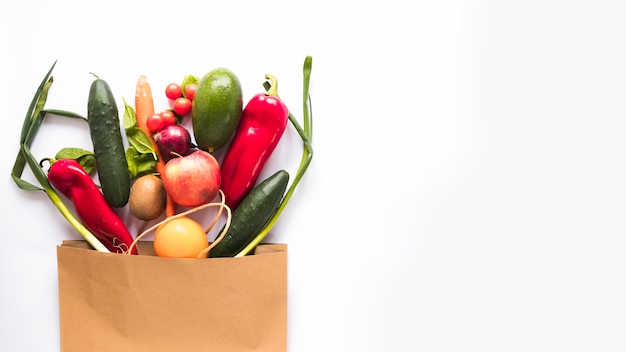 Variety of vegetables in paper bag over white background Free Photo