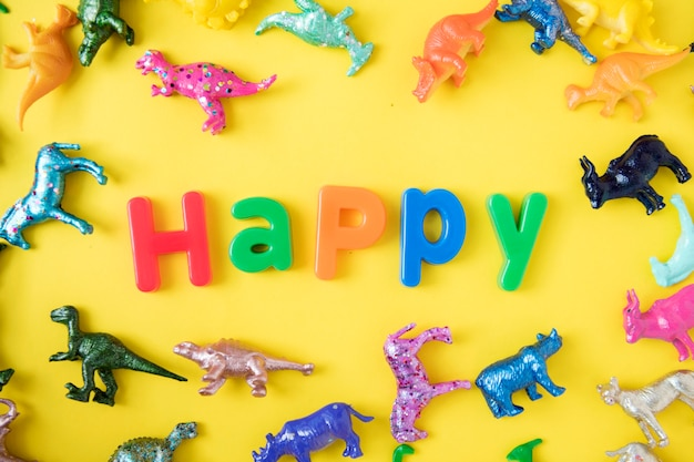Various animal toy figures background with the word happy Free Photo