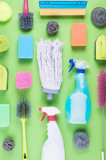 Various assorted cleaning equipments on green background Premium Photo