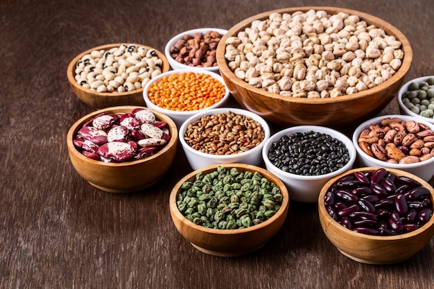 Various assortment set of indian legumes in bowls on wooden background with copyspace. Premium Photo