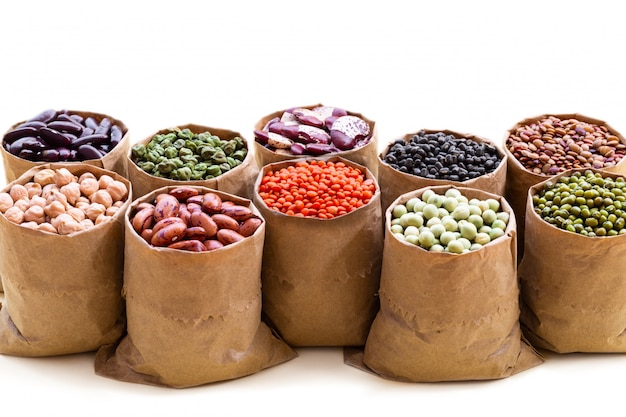 Various assortment set of indian legumes in paper sack bags isolated on white background. Premium Photo