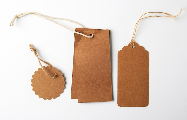 Various brown paper tags with ropes on white background Premium Photo