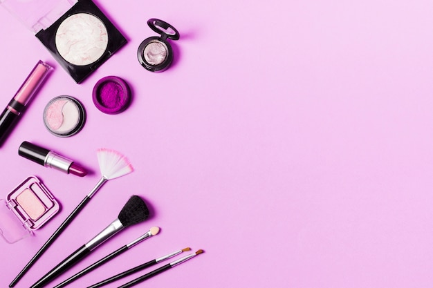 Various brushes and cosmetics in purple tint Free Photo