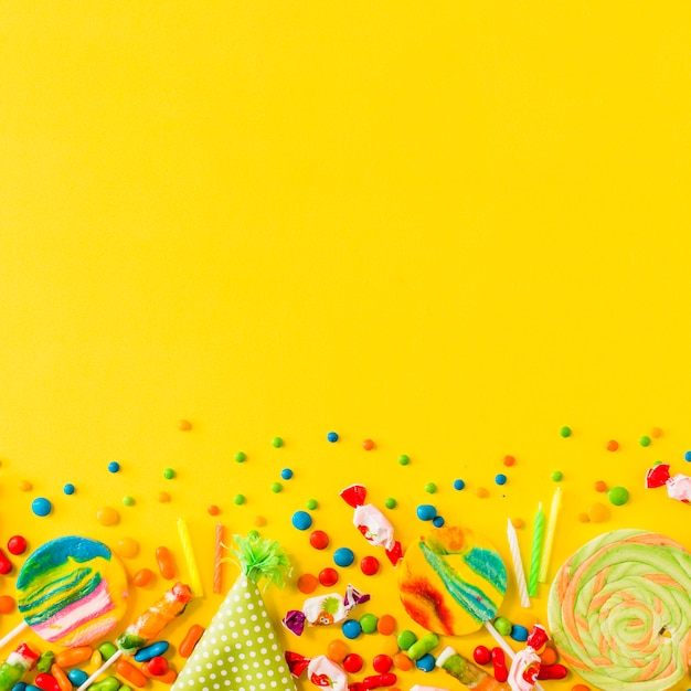 Various candies and party hat at the bottom of yellow background Free Photo