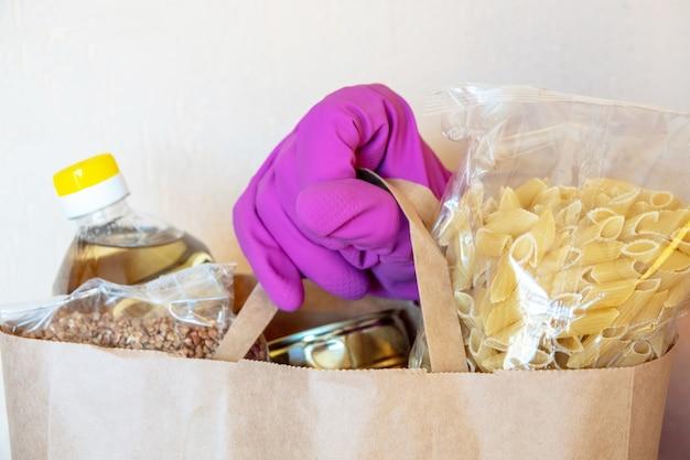 Различные консервы, макароны и крупы в картонной коробке. продовольственные пожертвования или концепция доставки еды. Premium Фотографии