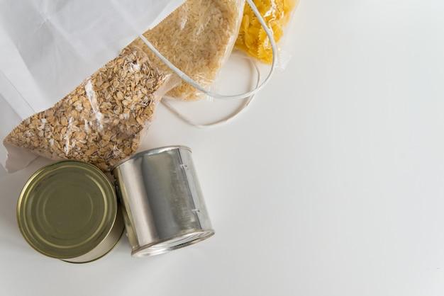 Различные консервы, макаронные изделия, рис и сырые зерна злаков на столе в бумажном пакете с местом для копирования Premium Фотографии
