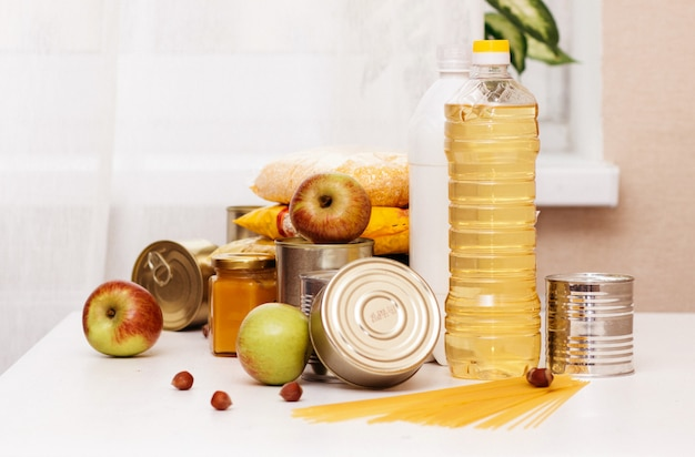 Various canned goods, pasta and cereals on a white table. food donation or food delivery concept. Premium Photo