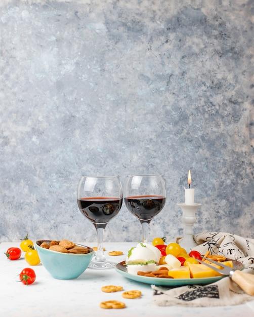 Различный сыр и сырная тарелка на светлом столе с различными орехами и фруктами и бокалом вина Бесплатные Фотографии
