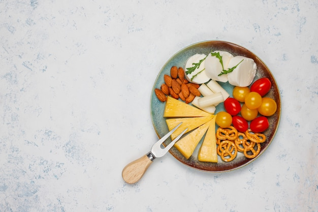 Various cheese and cheese plate on light table with different nuts and fruits Free Photo