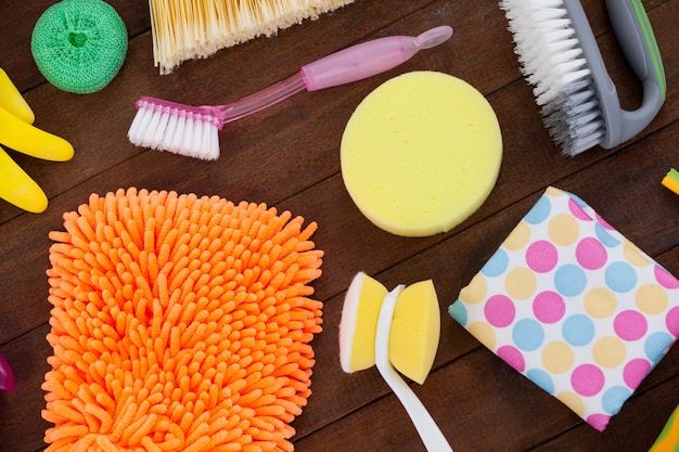 Various cleaning equipment arranged on wooden floor Premium Photo