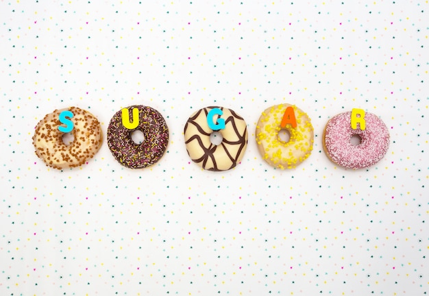 Различные цветные вкусные пончики со словом «сахар», концепция празднования. вид сверху Premium Фотографии