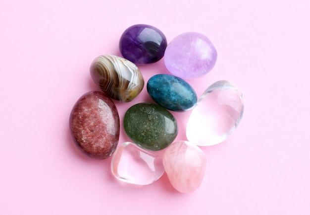 Драгоценные камни разного цвета, необработанные и обработанные. аметист, розовый кварц, агат, апатит, авантюрин на розовой стене. Premium Фотографии
