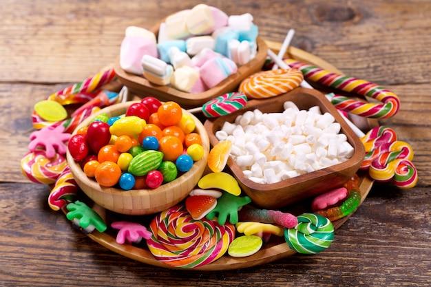 나무 테이블에 다양한 다채로운 사탕, 젤리, 막대 사탕, 마시맬로 및 마멀레이드 프리미엄 사진