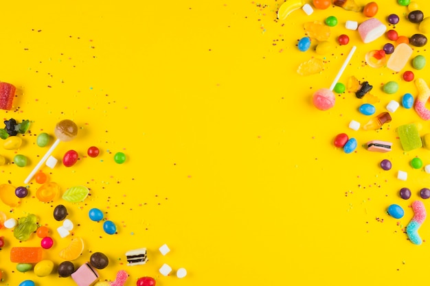 Various colorful candies and lollipops on yellow surface Free Photo