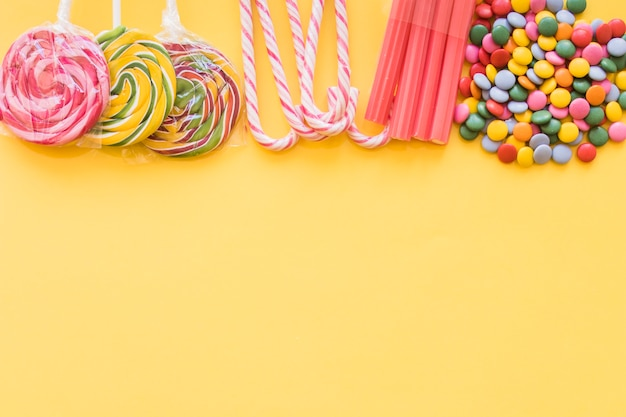 Various colorful candies on the yellow backdrop Free Photo