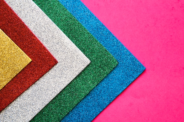 Various colorful carpets on pink background Free Photo