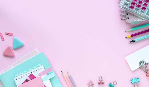 Various colorful stationery for school and office on pink background with copyspace Free Photo