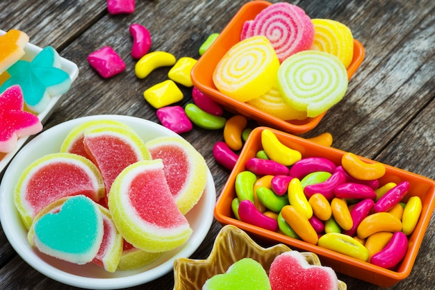 Various colorful sugary candy in container on old wooden plank Premium Photo