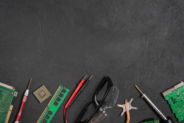 Various computer parts; digital multimeter and safety glasses on black background Free Photo