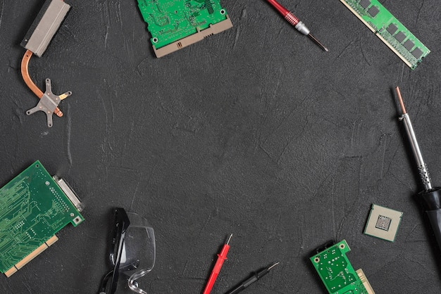 Various computer parts with tools on black backdrop Premium Photo