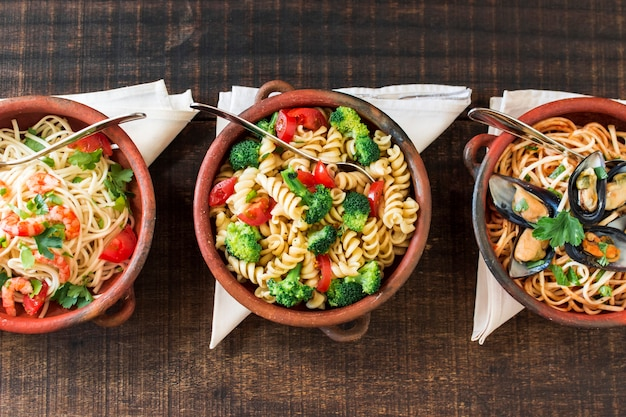 Various cooked pasta in the earthenware with folded napkin on wooden table Free Photo
