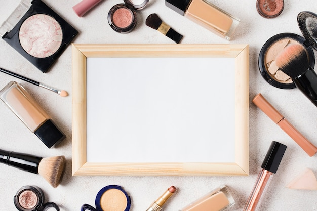 Various cosmetics and blank frame scattered on light background Free Photo