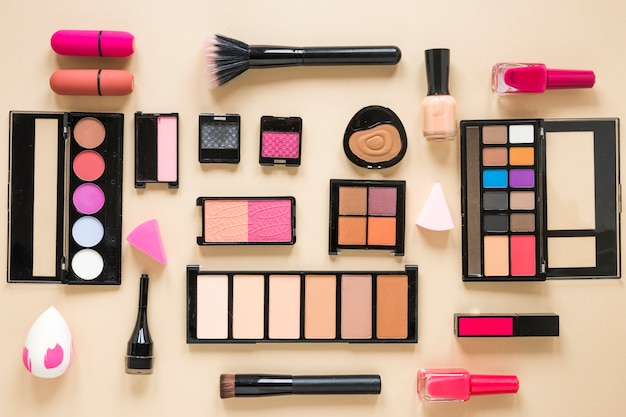 Various cosmetics types scattered on beige table Free Photo