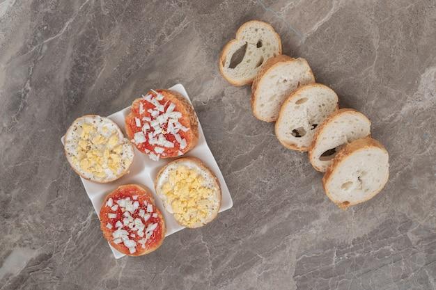パンのスライスと白いプレート上の様々なおいしいブルスケッタ。高品質の写真 無料写真