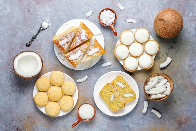 さまざまなおいしいココナッツのお菓子、クッキー、ケーキ、マシュマロ、ココナッツフレーク、半分のココナッツ、トップビュー 無料写真