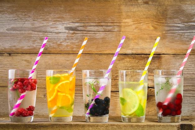 Various detox water in glasses, different tastes, berries, fruits. Premium Photo