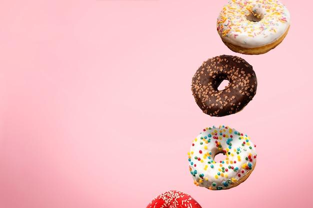 Различные пончики летают в воздухе изолированные Premium Фотографии