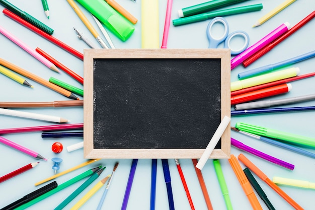 Various drawing tools scattered around blank chalkboard on blue desk Free Photo