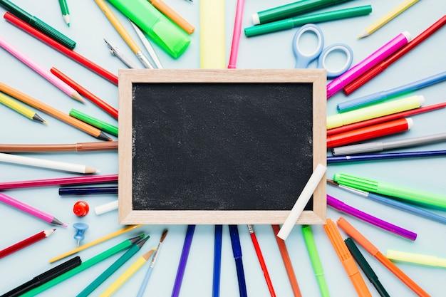 青い机の上の空白の黒板の周りに散らばって様々な描画ツール 無料写真