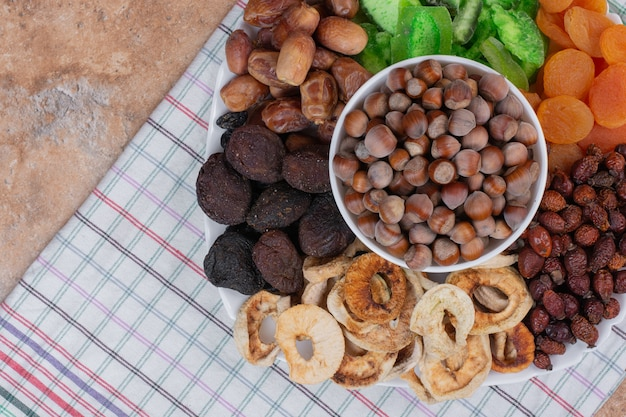 Various dried fruits and nuts on white plate. Free Photo