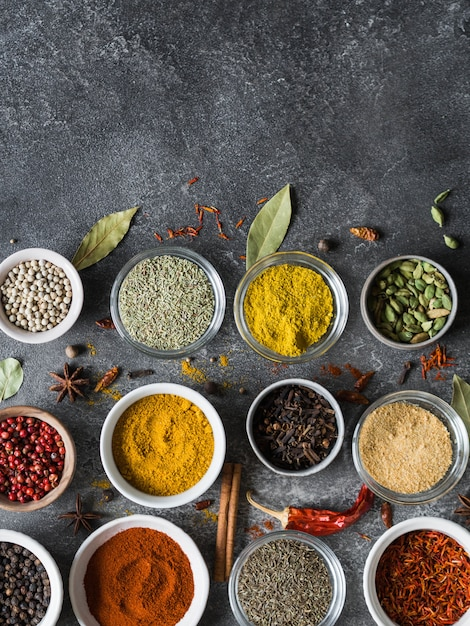 Various dry spices flat lay in small bowls on gray background. top view, copy space Premium Photo