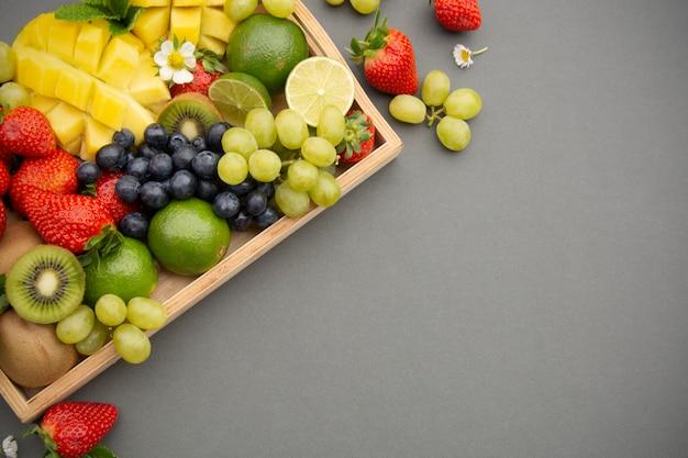Various fresh fruits - mango, grapes, tangerine, lime, strawberry, kiwi, mint. Premium Photo