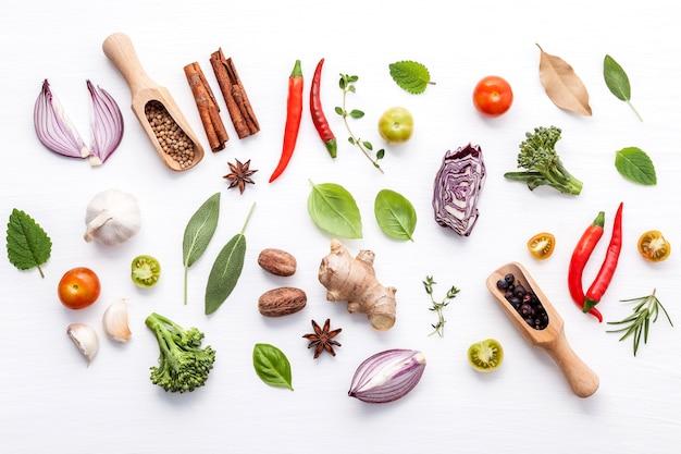 Различные свежие овощи и травы на белом фоне Premium Фотографии