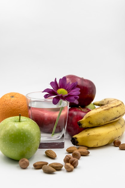 Various fruits; hazelnut; almond with glass of water and flower in white background Free Photo